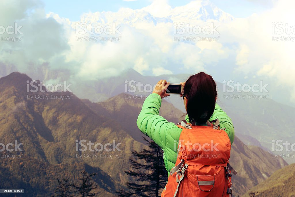 young asian woman backpacker taking photo with smartphone stock photo