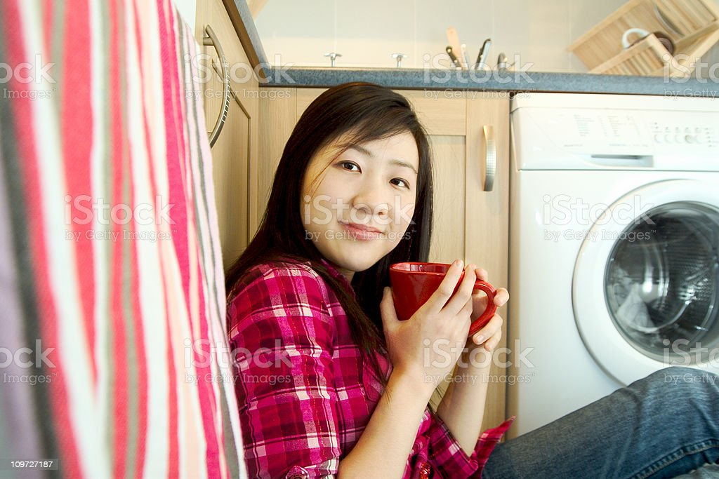 Young Asian Woman Drinking Coffee on Floor of Kitchen royalty-free stock photo