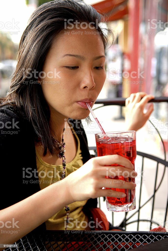 Young Asian Woman Drinking Cranberry Juice at Sidewalk Cafe stock photo
