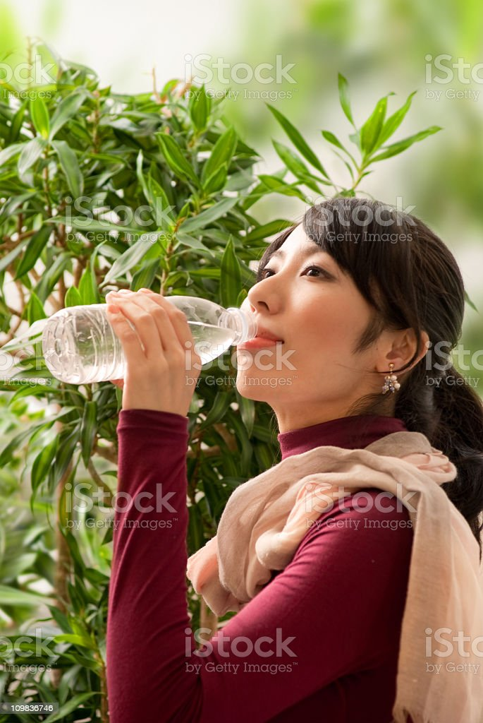 young Asian woman drinking water with tree background stock photo