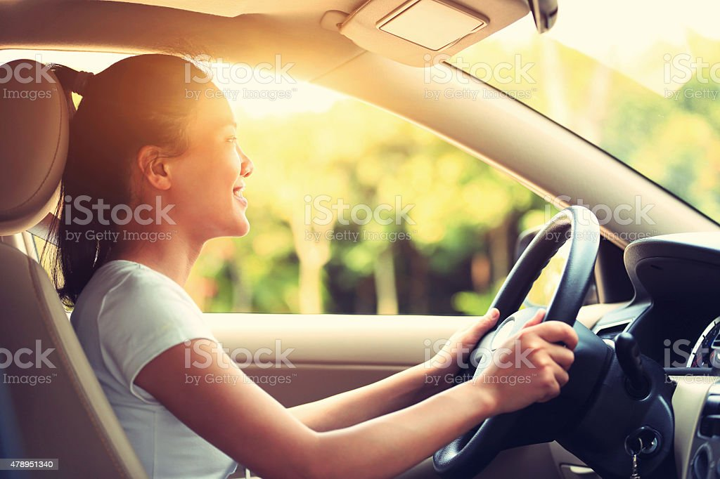 young asian woman driver driving a car stock photo