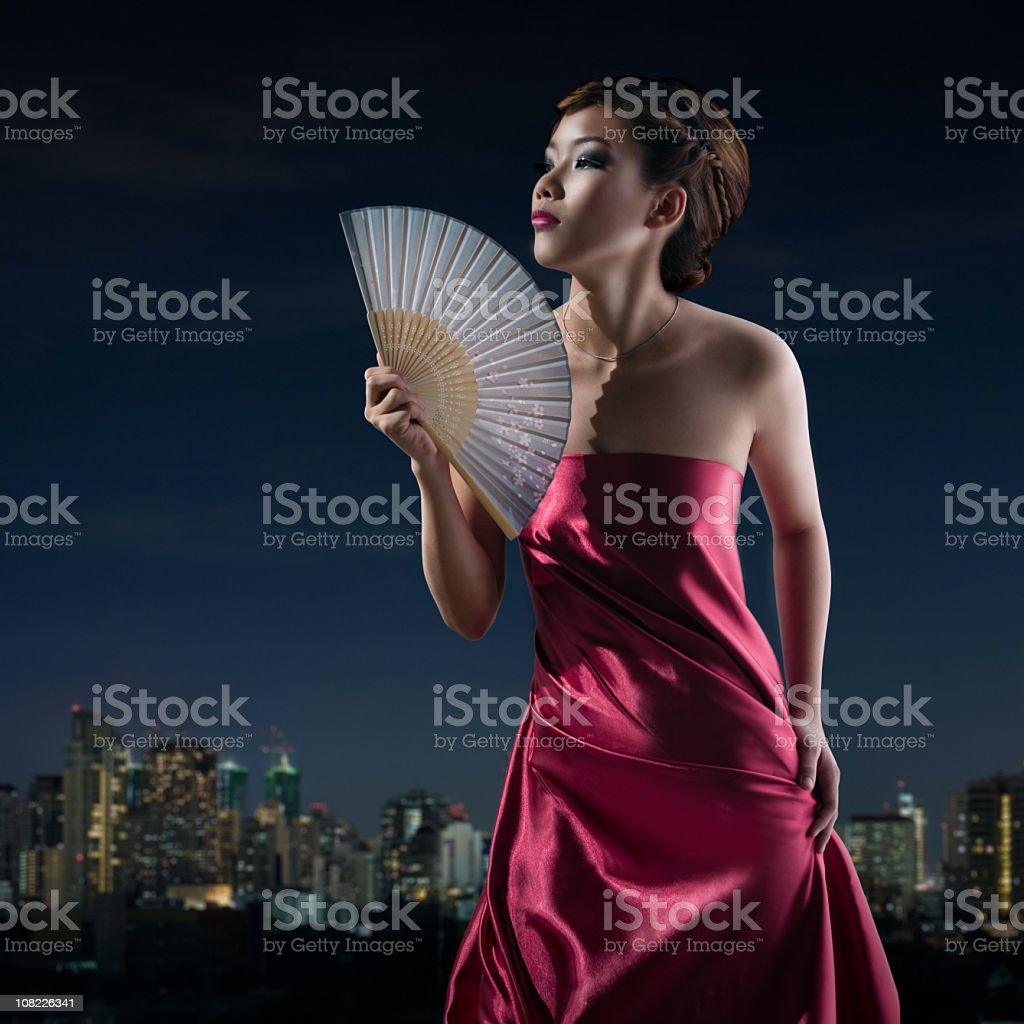Young Asian Woman Fanning Herself, Bangkok Skyline Background royalty-free stock photo