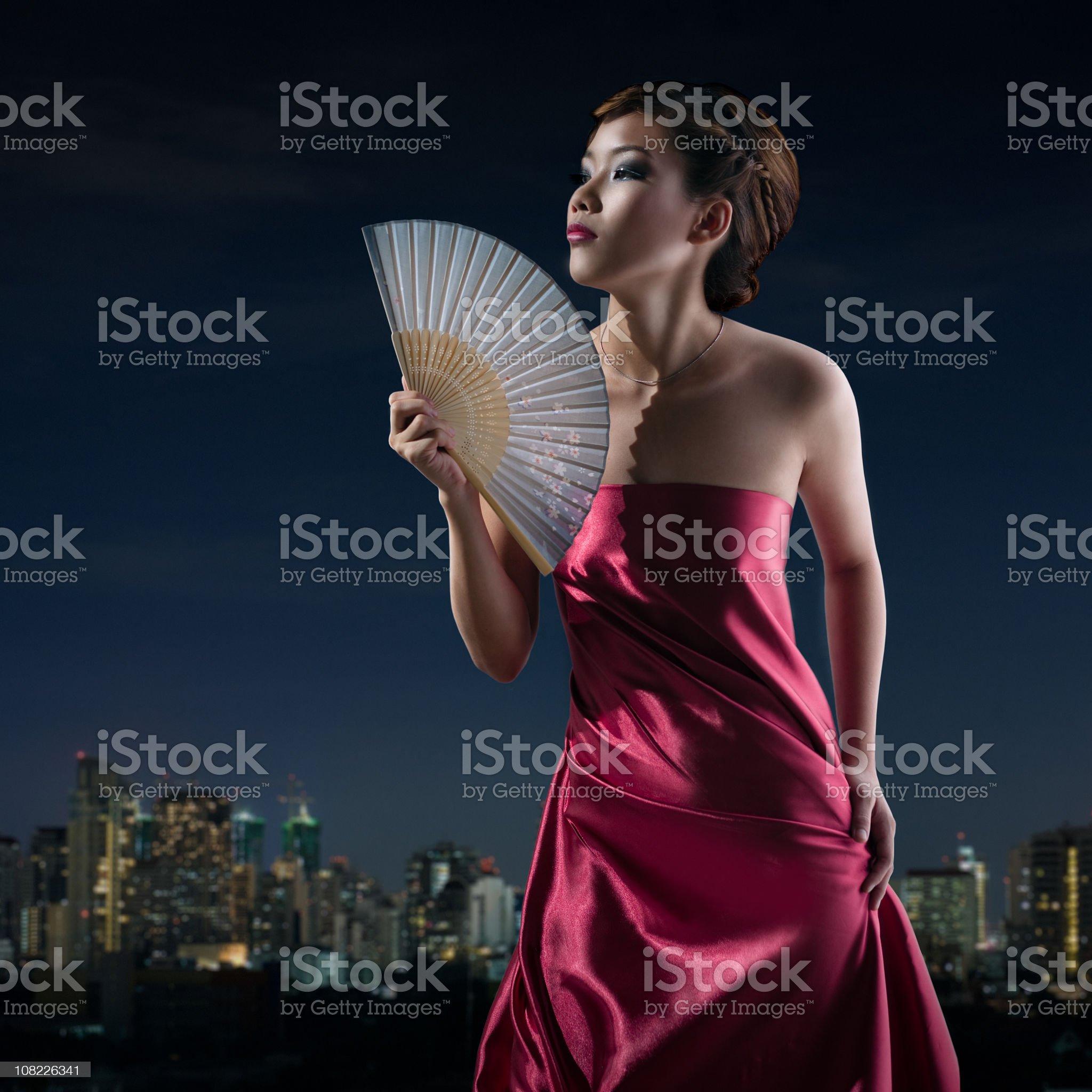 Young Asian Woman Fanning Herself, Bangkok Skyline Background royalty-free stock photo