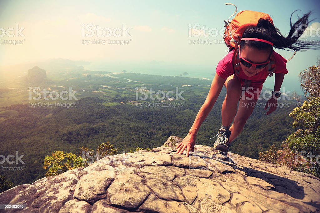 young asian woman hiker climbing rock on mountain peak cliff stock photo