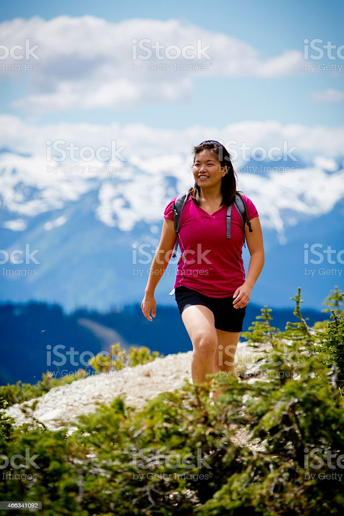 Young Asian woman hiking in mountains. stock photo