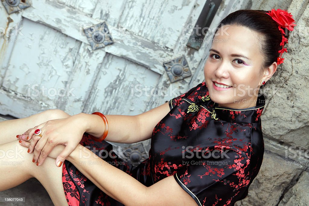 Junge asiatische Frau in chinesische Kleid vor Steinmauer Lizenzfreies stock-foto
