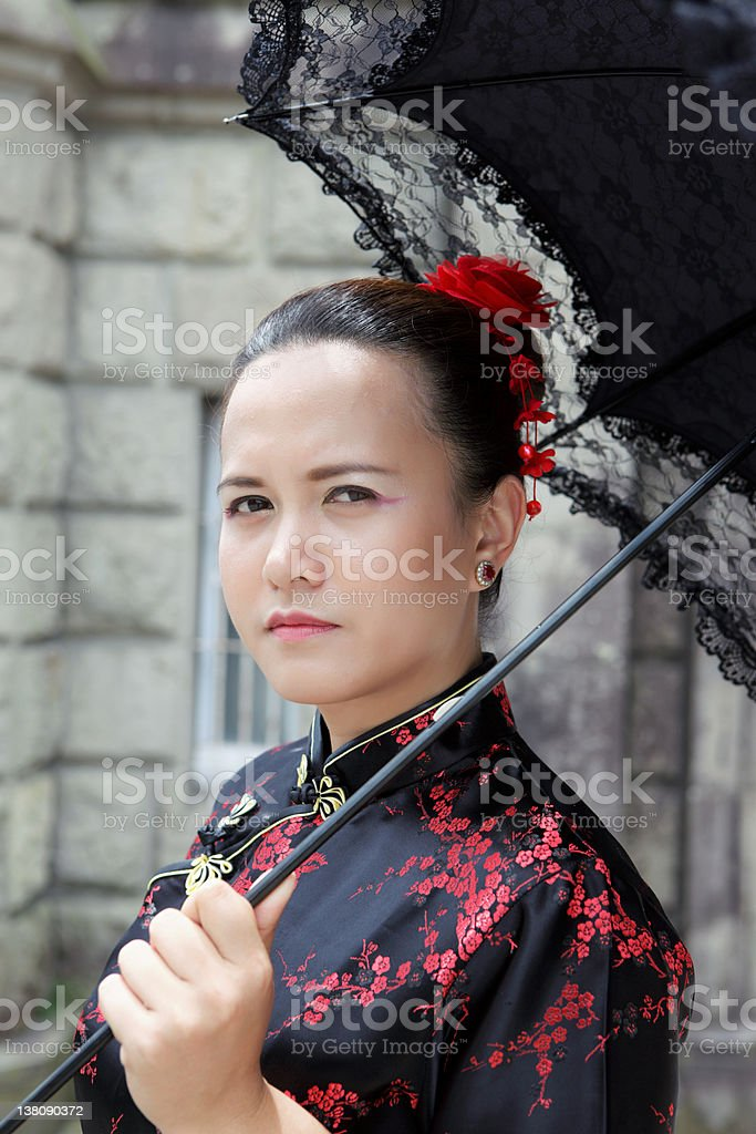 Young Asian woman in Chinese dress holding a black umbrella royalty-free stock photo