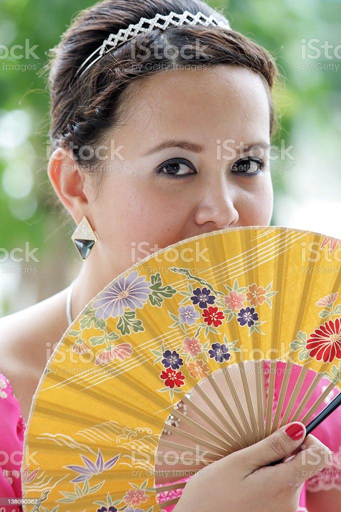 Junge asiatische Frau im rosa Kleid hält ein fan der gelben Lizenzfreies stock-foto