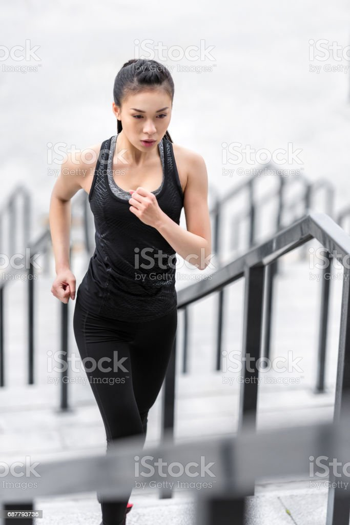 Young asian woman in sportswear running up on stadium stairs stock photo