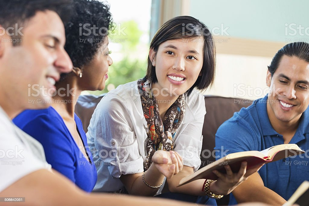 Young Asian woman leading Bible study group at home stock photo