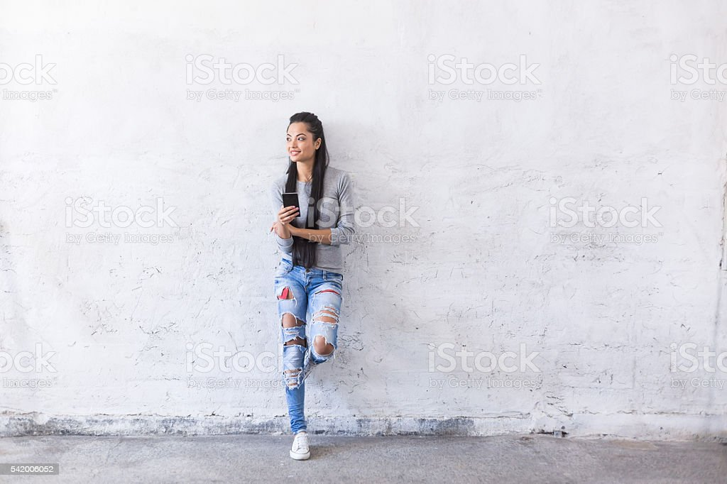 Young asian woman leaning on blank wall stock photo