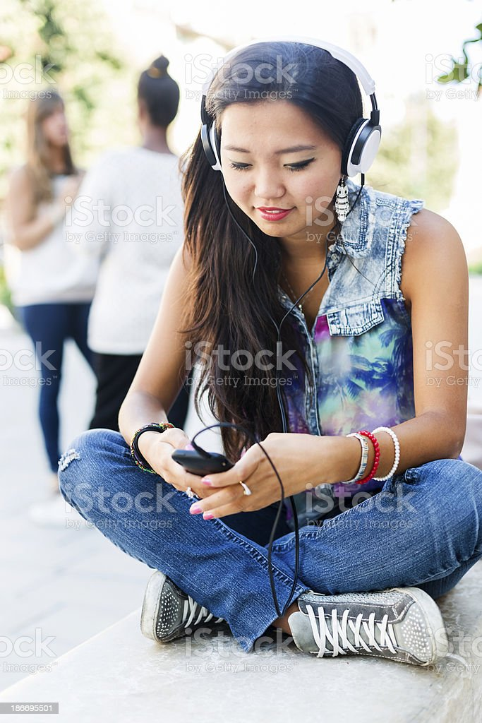 Young asian woman listening music from smartphone royalty-free stock photo