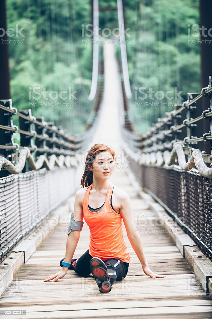 Young asian woman making splits on rope bridge stock photo