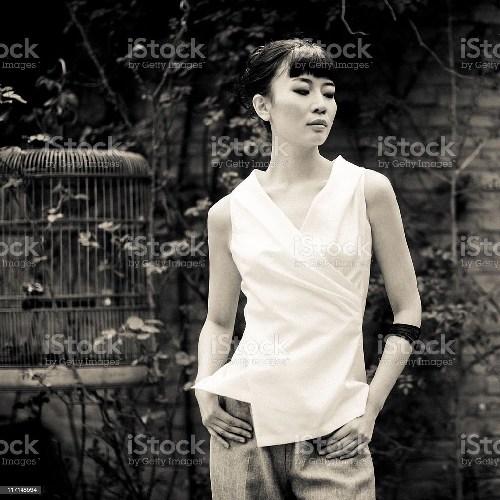 Young asian woman next to bird cage royalty-free stock photo