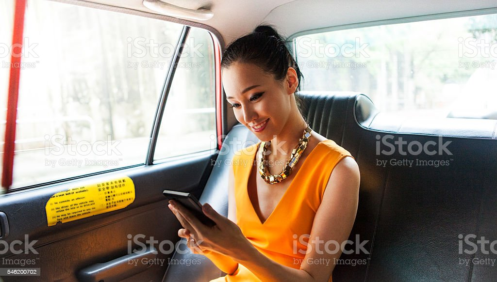 Young Asian Woman On Taxi Chatting With Friends Online stock photo