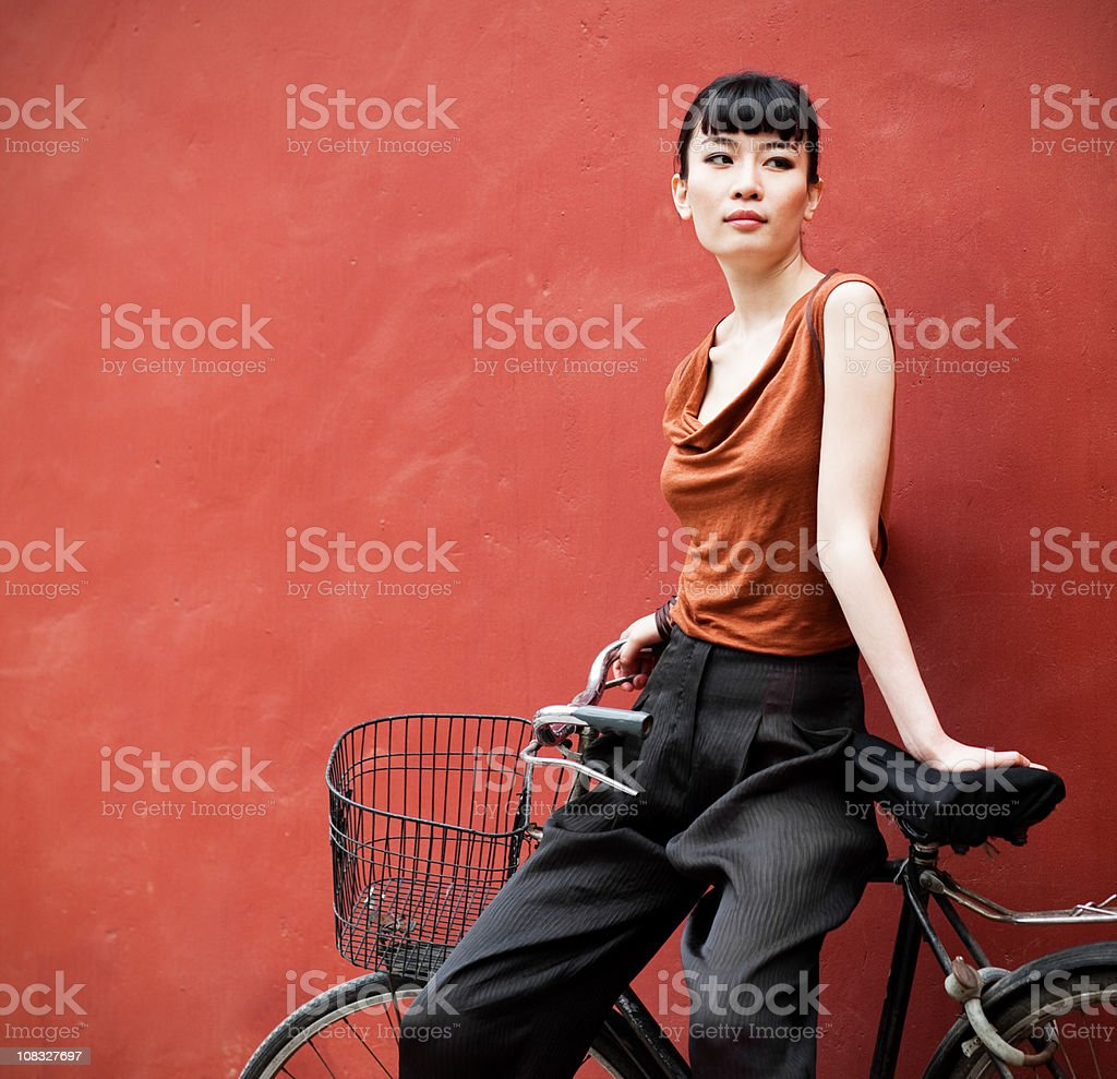 Young asian woman posing sitting on bicycle stock photo