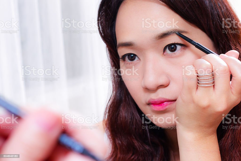 young asian woman putting make up in front of mirror. stock photo
