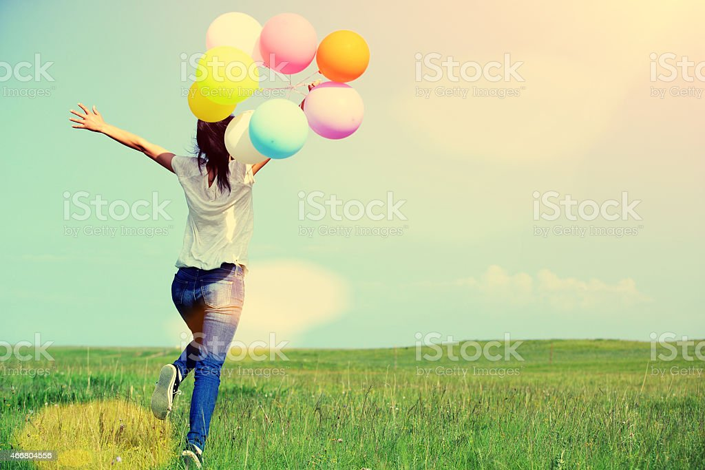 young asian woman running and jumping with colored balloons stock photo