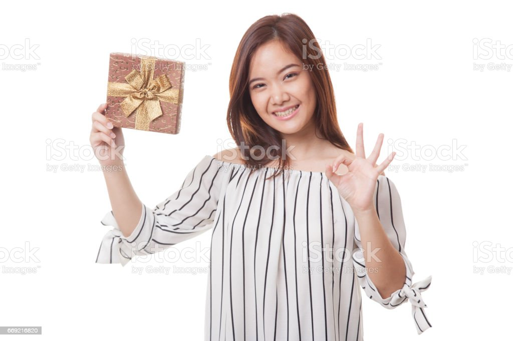 Young Asian woman show OK with a gift box. stock photo