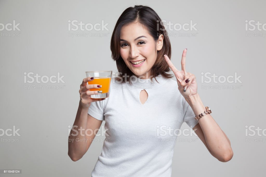 Young Asian woman show victory sign drink orange juice. stock photo