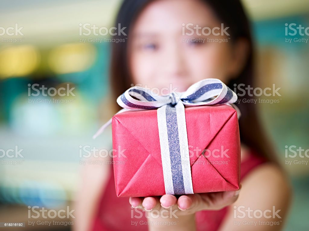 young asian woman showing a wrapped gift stock photo