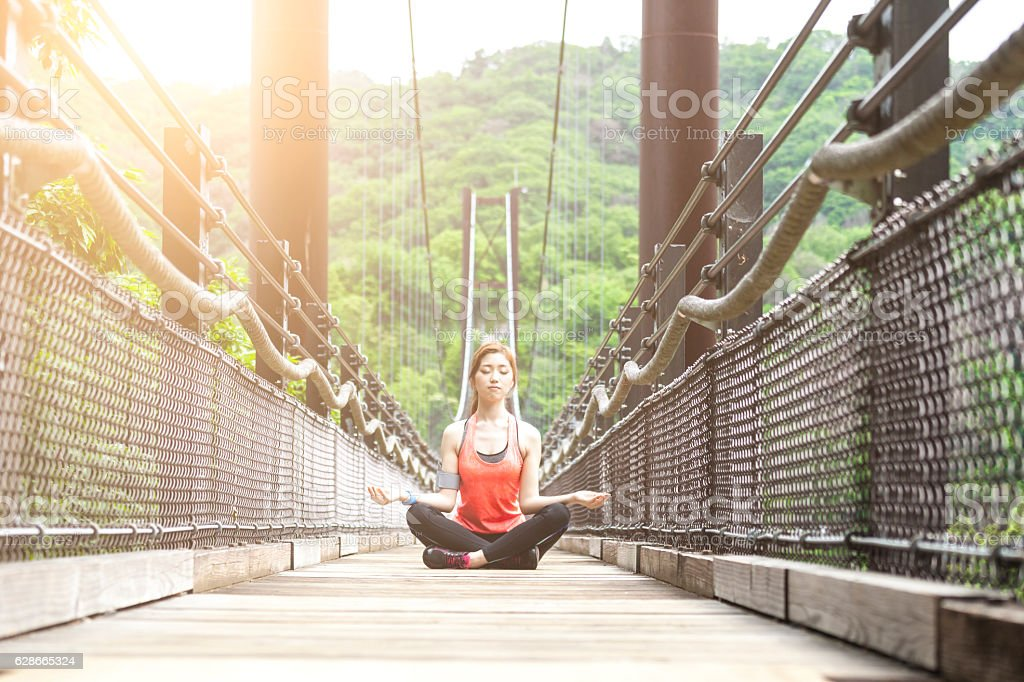 Young asian woman sitting in lotus position on rope bridge stock photo