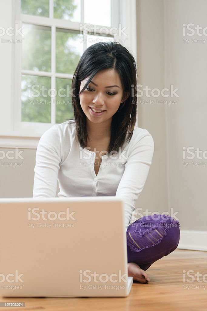 Young Asian Woman Using a Laptop Computer on Floor Vt royalty-free stock photo