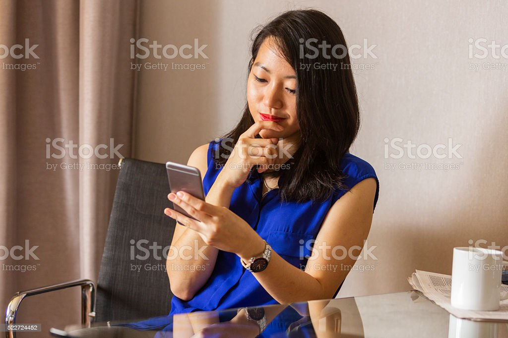 Young Asian Woman Using a Mobile Phone Indoors stock photo