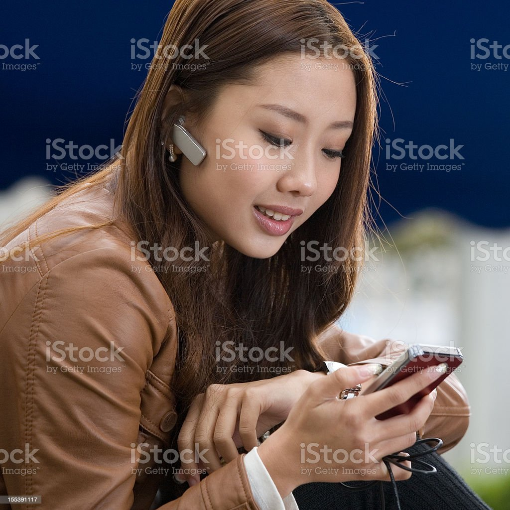 young asian woman using bluetooth and palmtop in bar royalty-free stock photo