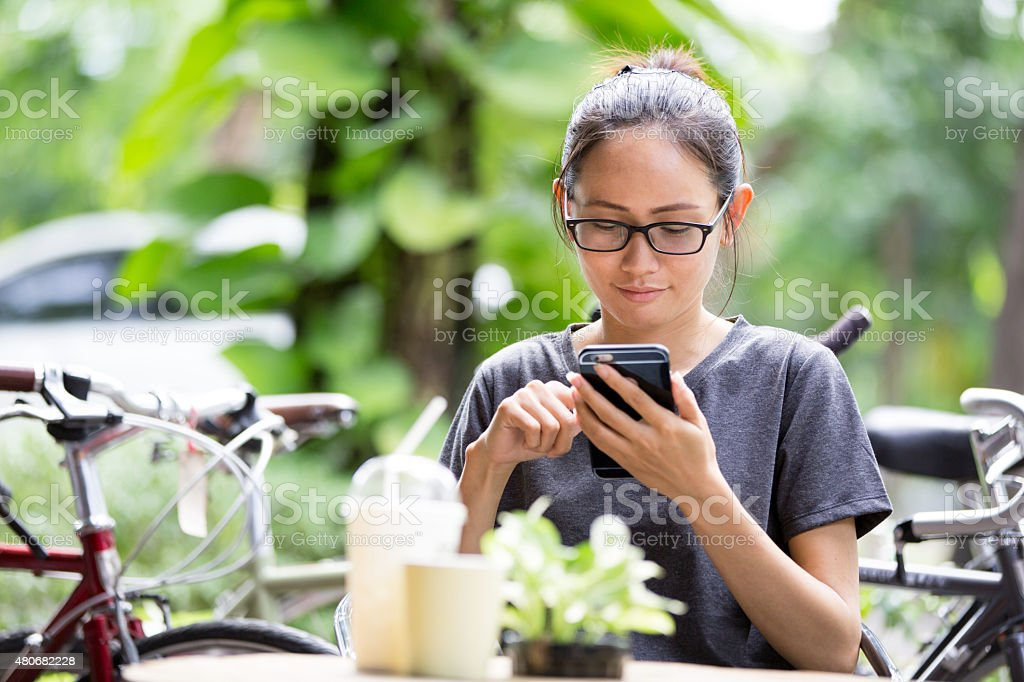 Young Asian woman  using smartphone in garden stock photo