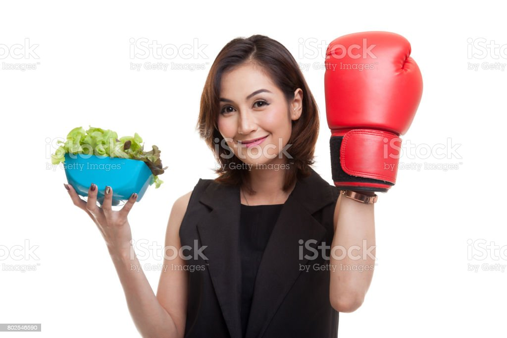 Young Asian woman with boxing glove and salad. stock photo