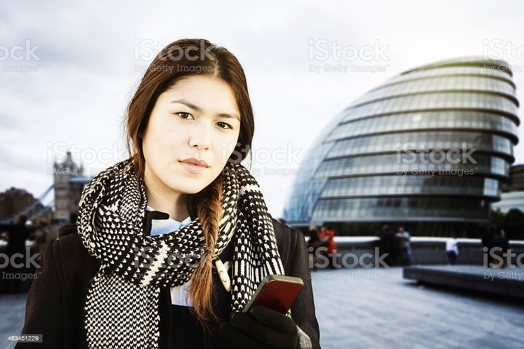 Young Asian woman with phone in front London City Hall stock photo