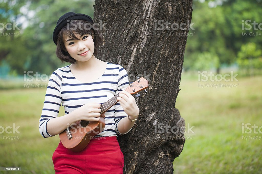 Young asian women playing ukulele in park, outdoor stock photo