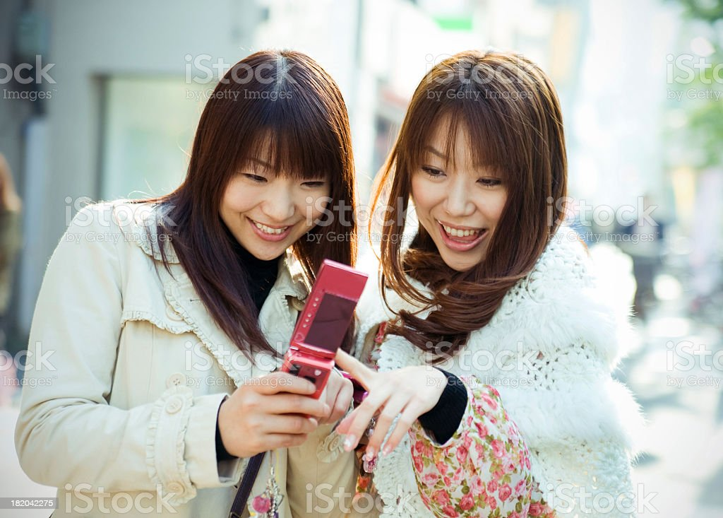 Young Asian women smiling with pink mobile phone stock photo