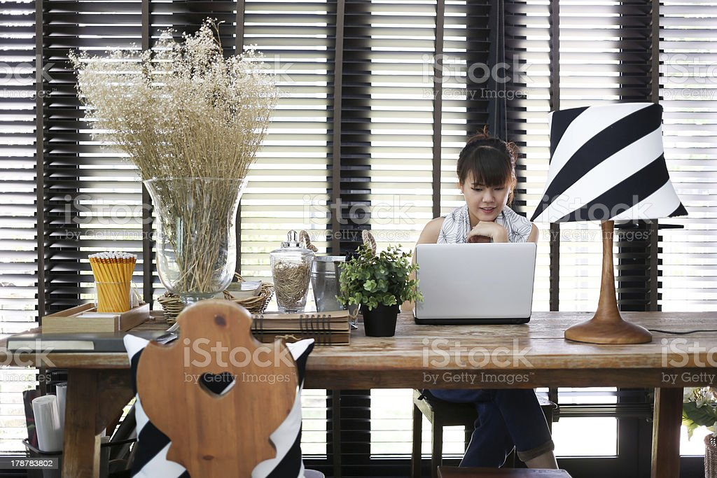 Young asian working woman is using a laptop stock photo