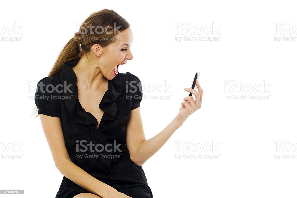 Young astonished woman holding a cellphone on white background studio royalty-free stock photo