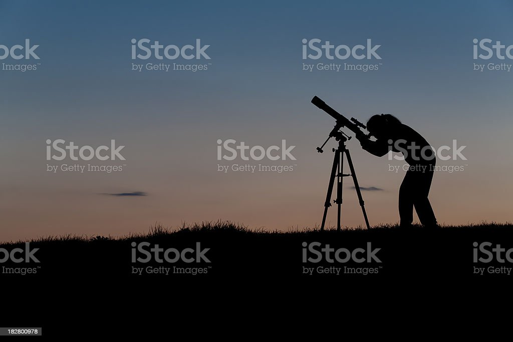 Young astronomer with telescope in night sky stock photo