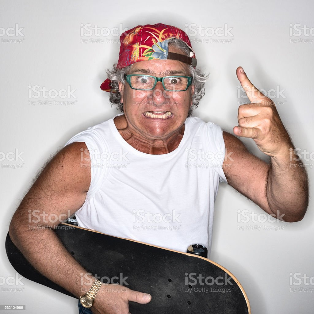 Young at heart grandpa with skateboard and rock and roll stock photo