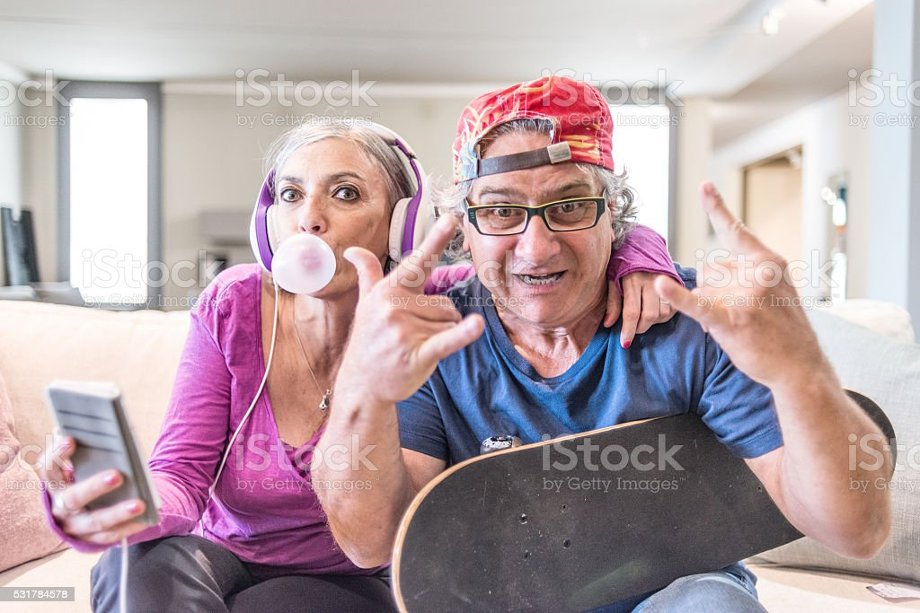 Young at heart grandparents series: Listening music and rock sign stock photo