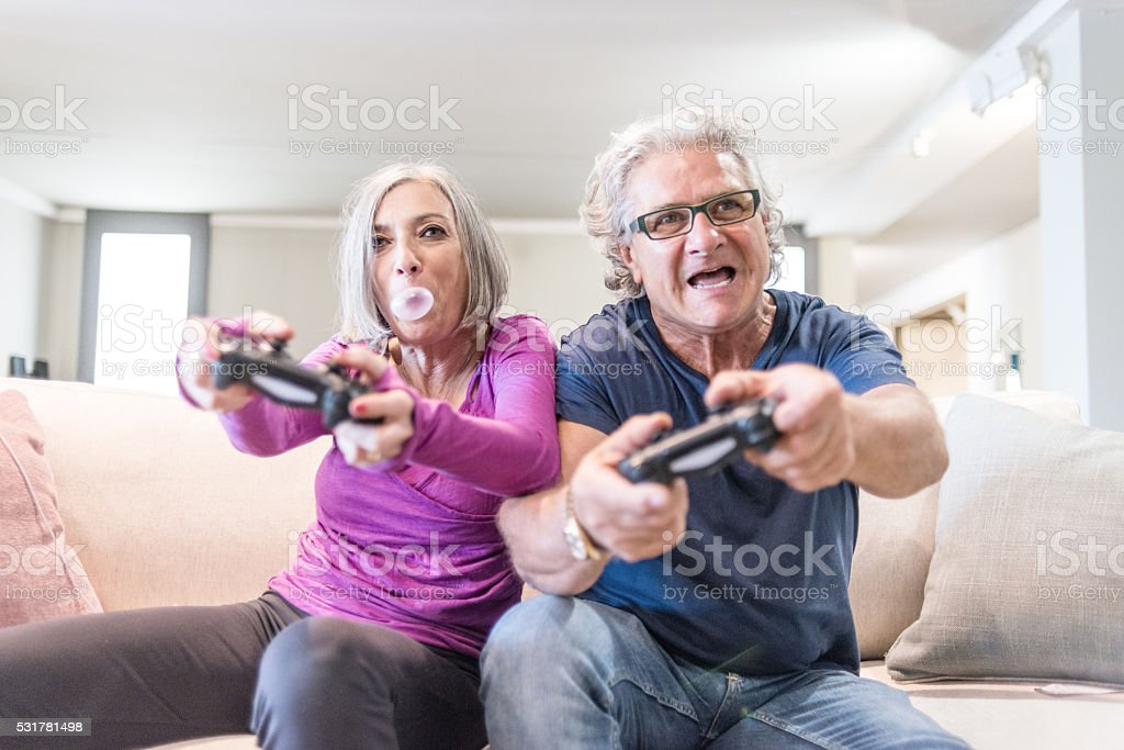 Young at heart grandparents series: Playing videogames stock photo