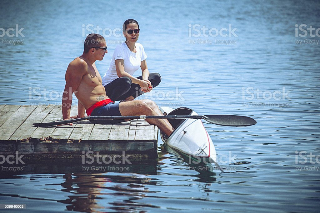 Young athlete and his coach preparing for kayak sprint training stock photo