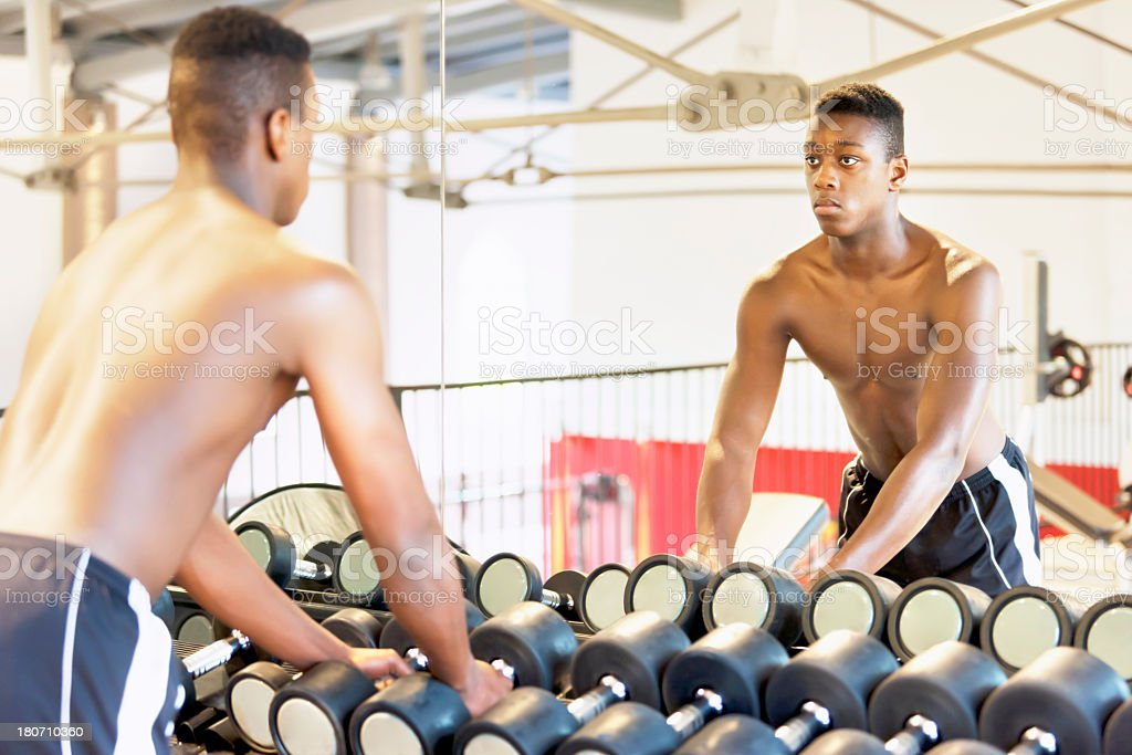 Young athlete choosing dumbbells stock photo
