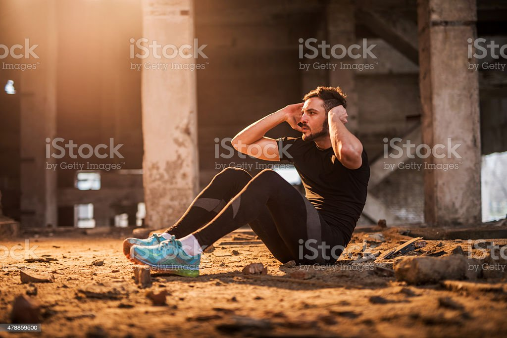 Young athlete doing sit-ups in a ruin. stock photo