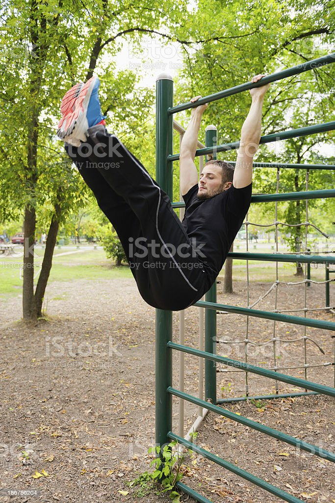Young athlete exercising on stall bars stock photo