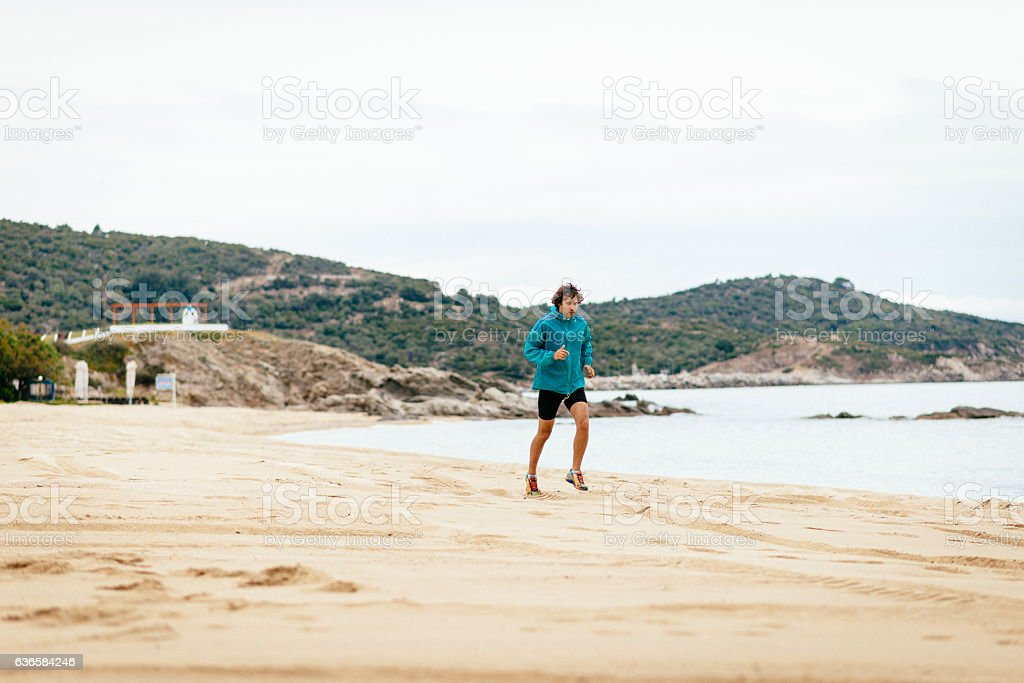 Young athlete jogging at the beach stock photo