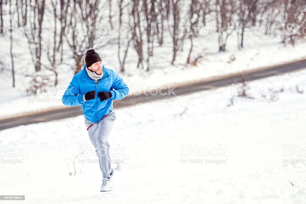 Young athlete man running on snow for a healthy training stock photo