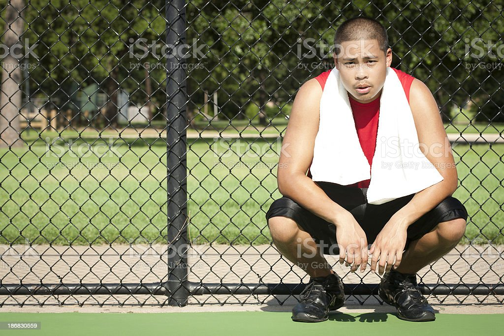 Young Athlete Resting at a Court Fence royalty-free stock photo