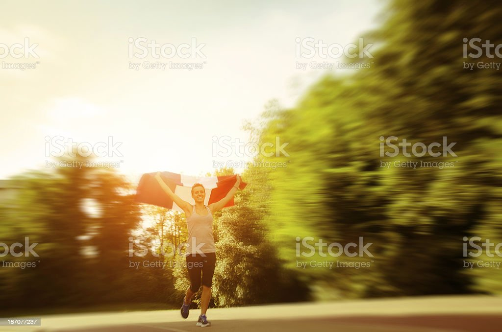Young athlete running fast waving a France flag royalty-free stock photo