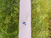 Young athlete running outside in sunny nature. Aerial view.
