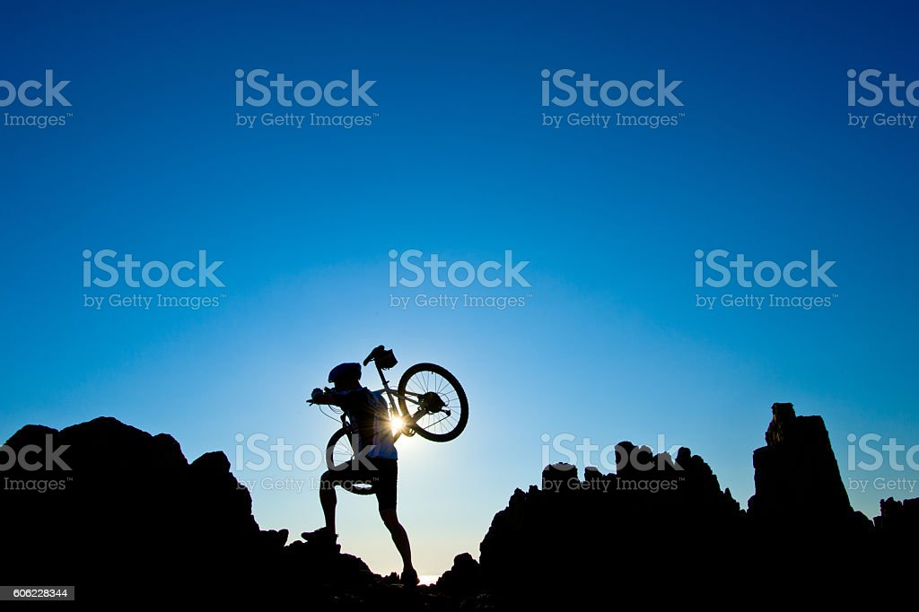 Young athlete standing on a rock with bicycle stock photo